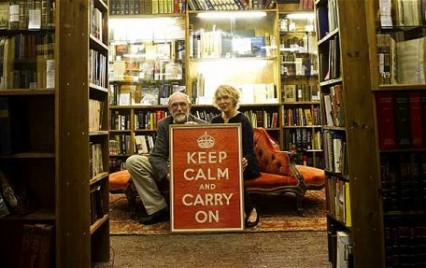Stuart and Mary Manley with the original poster in their shop, Barter Books.